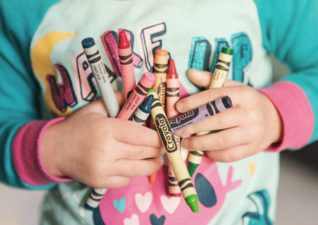 interior tips children - a picture of a toddler holding an armful of Crayola wax crayons